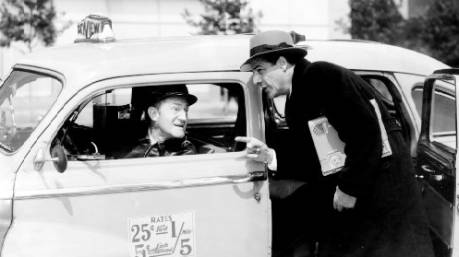A vintage photo of a man speaking with the driver of a taxicab